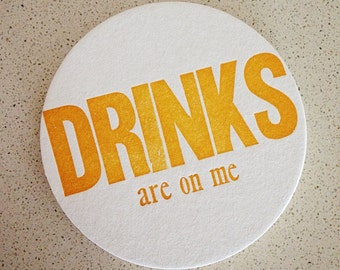 Set of eight 'Drinks are on me' letterpress coasters
