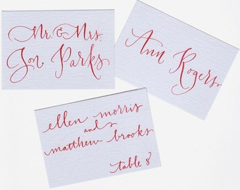 Blue and red place cards with calligraphy for wedding or event