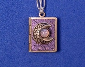 New Moon Peace Book, purple and silver, holding 14 words for peace from around the world