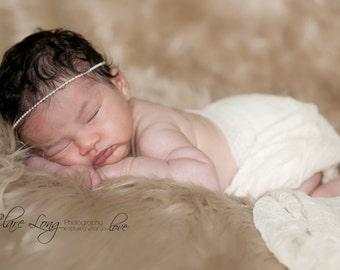 Newborn white beaded band.