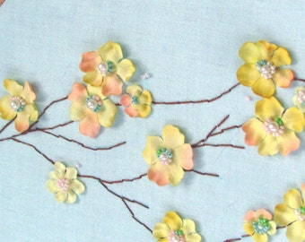 Hoop art of yellow blossom branch with beaded embroidered flower centers on pale blue fabric