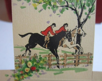Unused Edith Cherry 1930's die cut hand painted place card with graphics of 2 equestrians jumping over a country fence paper rosette accents