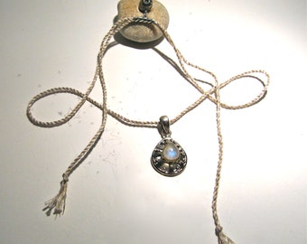 Wander to Wonder: rainbow moonstone and sterling silver pendant strung on handmade cord, finished with a pyrite skull and sterling clasp