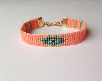 Evil eye woven beaded pastel salmon friendship bracelet.