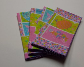 Set of 4 Easter cloth dinner napkins with Bunnies, Easter Eggs, Butterflies and Flowers trimmed in lavender.