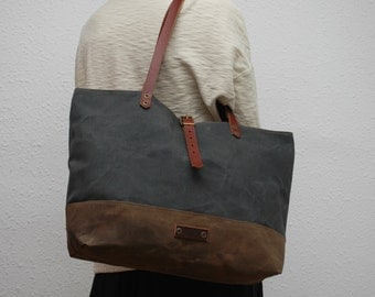 waxed canvas  bag , gunmetal gray color,brown ,with leather handles and closures,hand wax