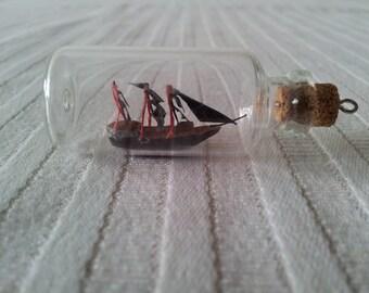 Black pirates boat in a bottle