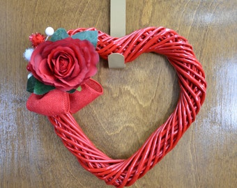 Red wooden heart wreath with a beautiful red rose, berries, and a red burlap bow.