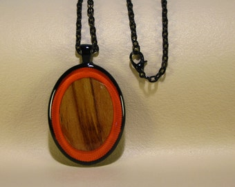 Spalted Maple oval on pumpkin orange background, resin encased in black finish pendant bezel with chain
