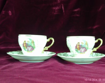 Vintage Set of 2 Tea Cups and Saucers white with Gold trim and picture of couple walking in a Garden