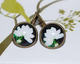 Closed dangling earrings white flower on black background