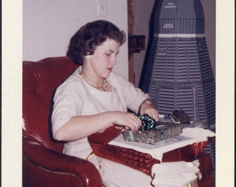 Vintage photo 1961 Woman Wraps Presents w Space Shuttle CApsule Behind Her