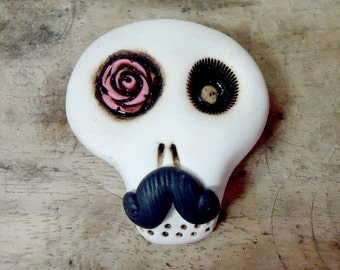White skull with black mustache and a pink rose in his eye. Dead gentleman. Brooch, keychain, pendant or magnet (you choose)