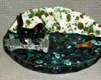 Black Lab chasing a stick handmade in U.S. from a lump of clay dish sold by Outsider Artist