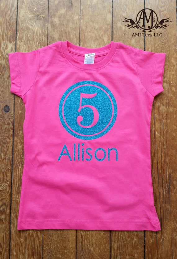 Princess Applique % Cotton T-Shirt. Personalized with Name and Age and has crystals on the crown and pink and white korkers on the sleeve.