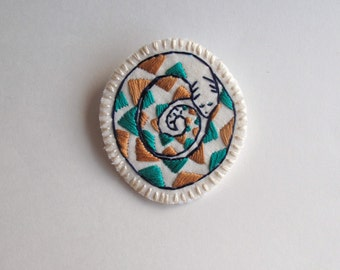 Snake brooch embroidered by hand with a geometric design on cream muslin with cream felt backing silver plated pin back