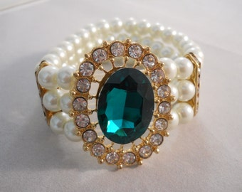 Reduced 3 Row Stretch Cuff Bracelet with White Pearls, Clear Rhinestones and a Large Green Crystal in a Gold Tone Frame