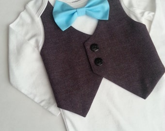 Baby Boy Bodysuit With A Dark Purple Vest Attached And A Blue  Bow tie.