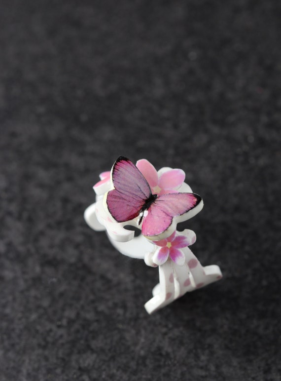 violet resin butterfly ring with cherry blossoms in white and soft pink polka dots, frilly flower statement ring with intricate details