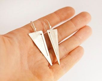 Long silver triangle earrings, lightweight, comfortable to wear, modern design with hand sawed pattern, brushed finish