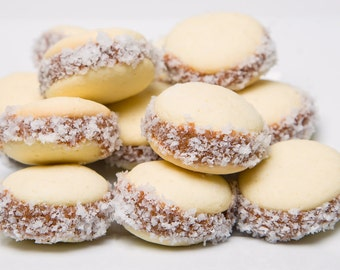 ALFAJORES DE MAIZENA. Two soft and delicious cookies filled with artisanal dulce de leche and rolled in shredded coconut.