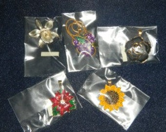 Five different pendants interchangeable on a 16 inch long gold tone chain.