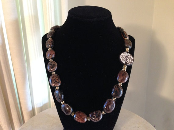 """23"""" necklace of dark Anipay seeds & accented w/ single 25mm Tree of Life round flat bone bead.  Beads are interspersed w/ brass chips."""