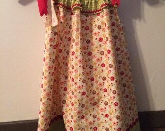 Pillowcase dress  has  ribbon ties at the shoulders.