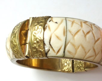 Heavy vintage carved bone bangle with stamped brass metal hinges