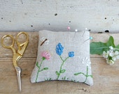 Rustic pincushion embroidered with flowers and a dragonfly. Natural organic linen and recycled cotton fabric