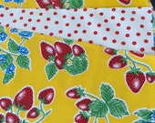 Reversible oilcloth placemats in a retro strawberries on lemon yellow and red polka dots