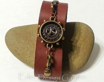Steampunk style leather and brass cuff bracelet with new and recycled watch parts in a brass bezel