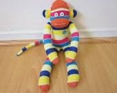 80s striped sock monkey plush with orange, magenta, blue, and yellow stripes