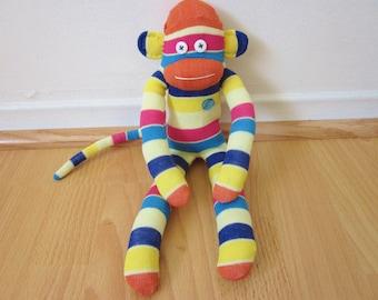 80s striped sock monkey plush with orange, magenta, blue, and yellow stripes
