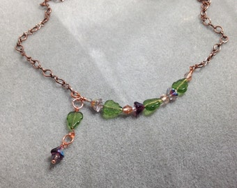 Purple flowers with leaves on an antiqued copper color chain