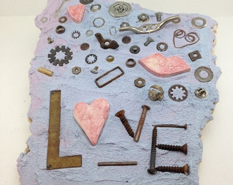 whimsical found object mosaic, LOVE spelled in hardware with a hand crafted ceramic heart, lavender, periwinkle and metal on scrap marble