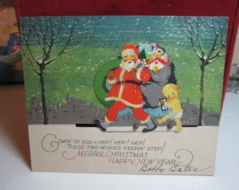 Colorful 1920's mechanical die cut P.F. volland christmas card santa claus and baby new year walking in snow city scape in the background