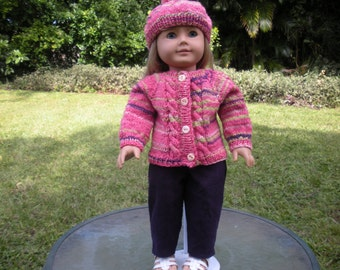 Pink sweater with random stripes in green, dark purple and white. The outfit includes a matching hat  and purple corduroy pants.