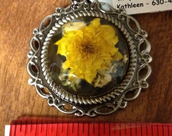 Real Flower.  Yellow mum is perfectly preserved in a round faceted resin piece.