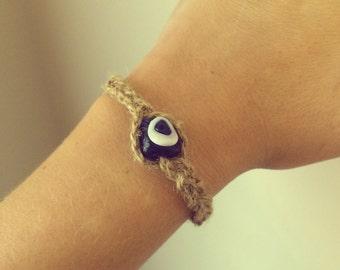 Hemp-ish rope braided around a glass evil eye bead