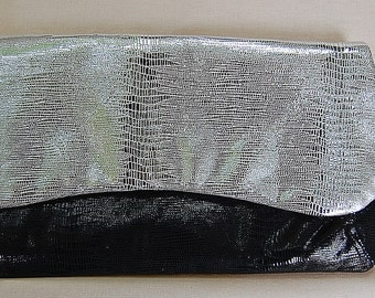 Black and silver clutch purse of embossed Italian lambskin, with a matching wrist strap and posh silver gray lining.