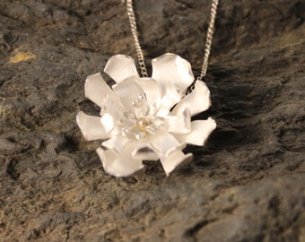 Sterling silver flower necklace with silver stamen and gold centre.