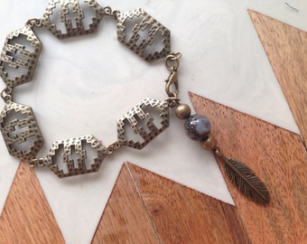 Metal cross bracelet with feather detail