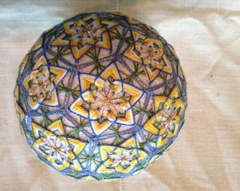 4 1/2  Japanese temari ball worked in yellow and blues