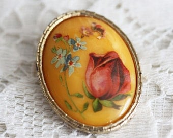 Oval vintage brooch with flower decoration