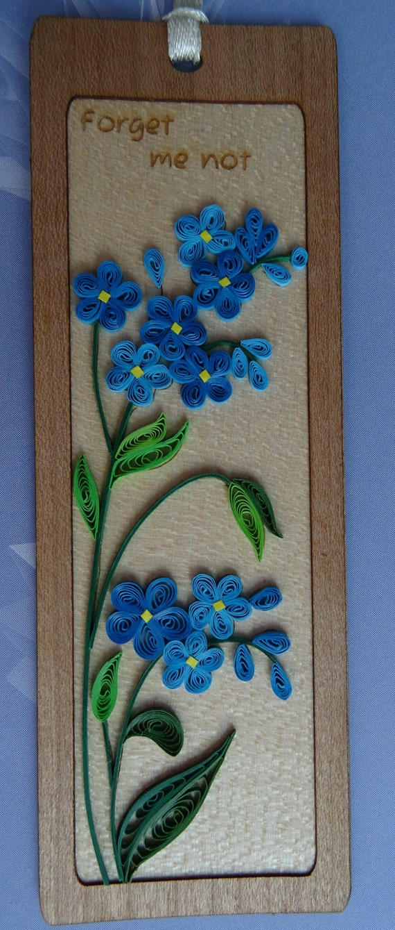 Bespoke handmade quilling bookmark. blue forget me not flower, quilling paper, wood background, quilling art and craft