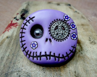 Hippie round skull in purple with a peace symbol in his eye and flowers on his face. Brooch, keychain, pendant or magnet (choose)