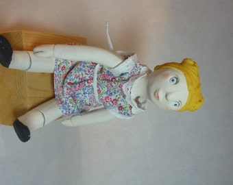 Doll articulated earthenware as formerly. Blonde hair, capped by two buttons.