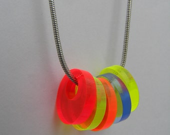 """Necklace Circles in Fluorescent Acrylic on Sterling Silver Snake Chain. Laser cut perspex, plexiglass. 16""""/18"""" snake chain. Made in the UK."""