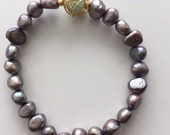 """The """"Polly"""" bracelet. Silver freshwater pearl bracelet with a wire wrapped aquamarine"""